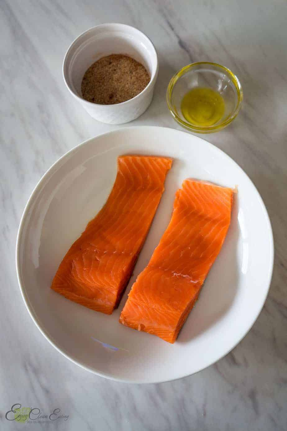 2 pieces of raw fish with  the seasoning cup and olive oil cup on the side