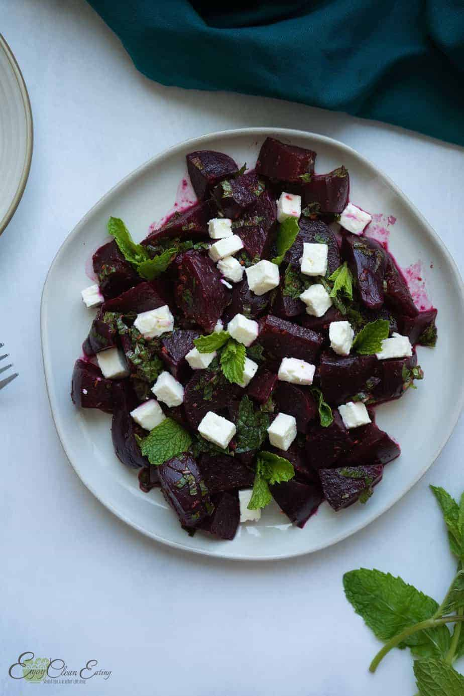 beet salad with feta cheese on a plate. a fork, small serving plate and napkins
