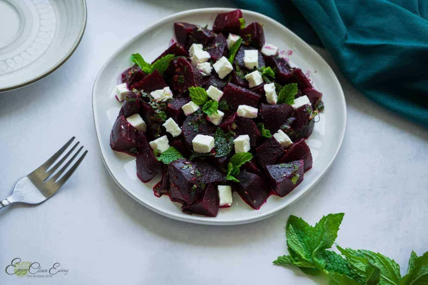 Feta and beet salad with fresh mint leave, a serving plate and a fork