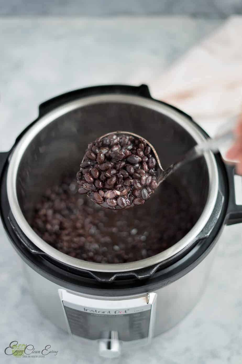 holding a soup serving spoon full of the fresh instant pot black beans