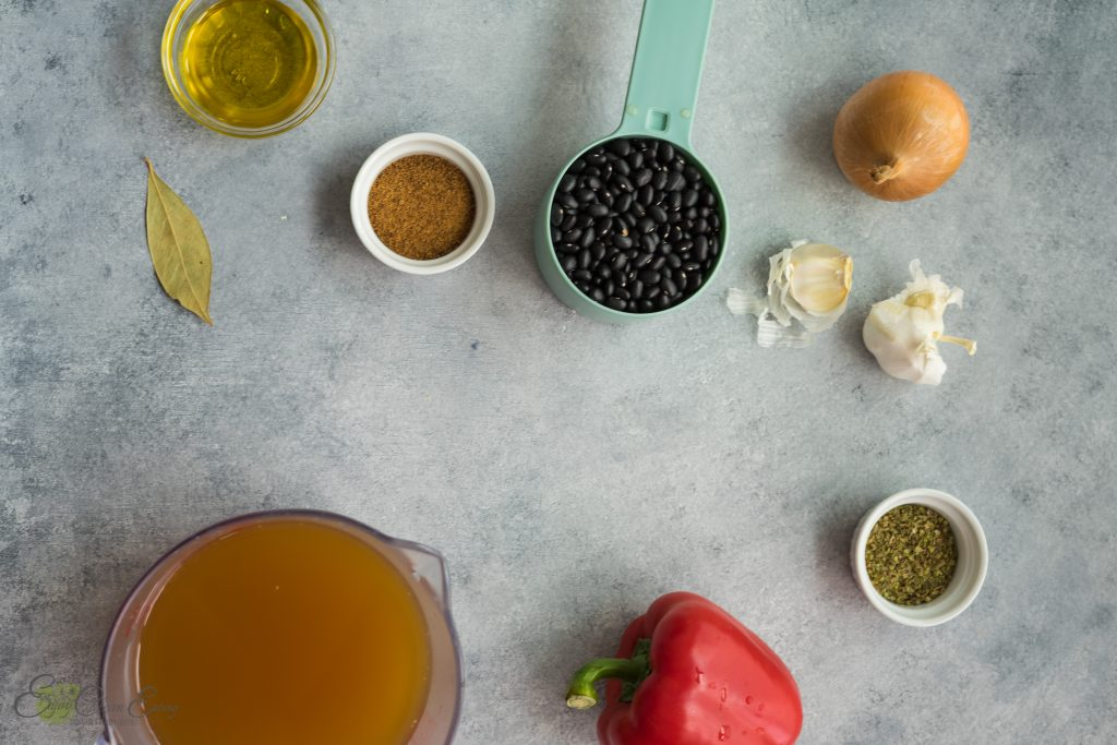 Ingredients to make cuban black beans in instant pot; onion, garlic, black beans, coconut sugar, bay leaf, olive oil, oregano, red bell pepper and vegetable broth.
