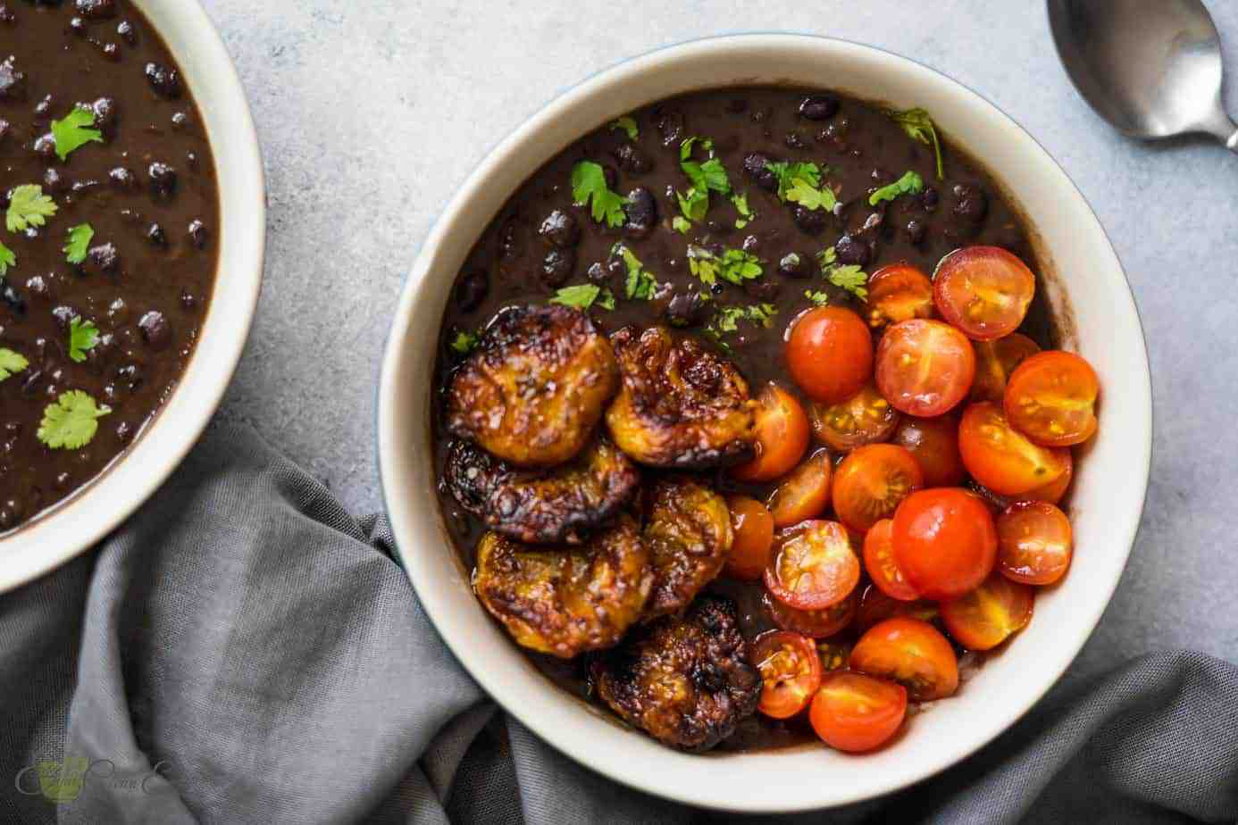 Two servings of instant pot cuban black beans with air fried plantains, tomatoes and sprinkle with fresh cilantro.