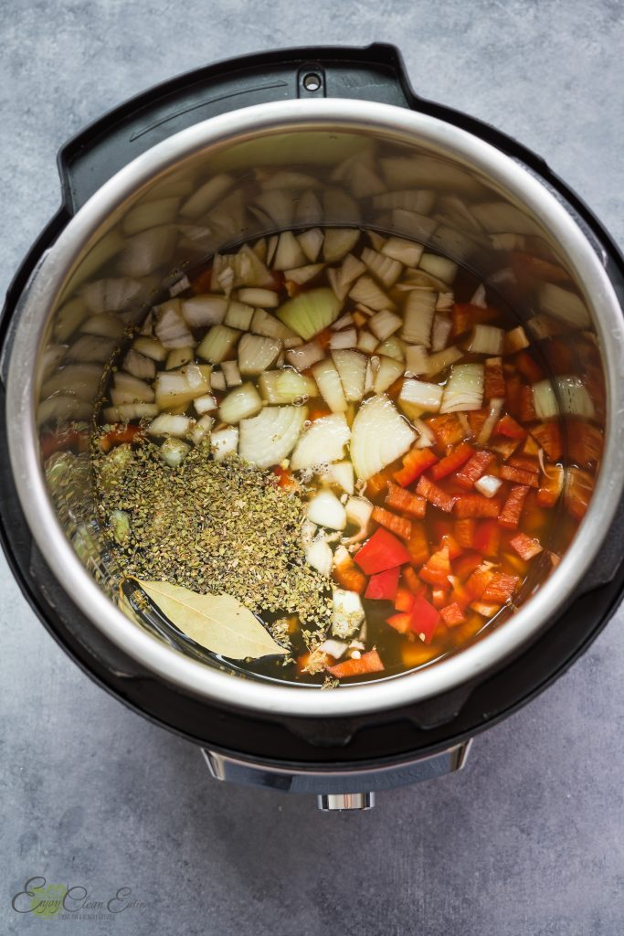 All the ingredients in the inner pot of the pressure cooker to make frijoles, onion, vegetable broth, oregano, bay leaf, bell pepper and garlic.