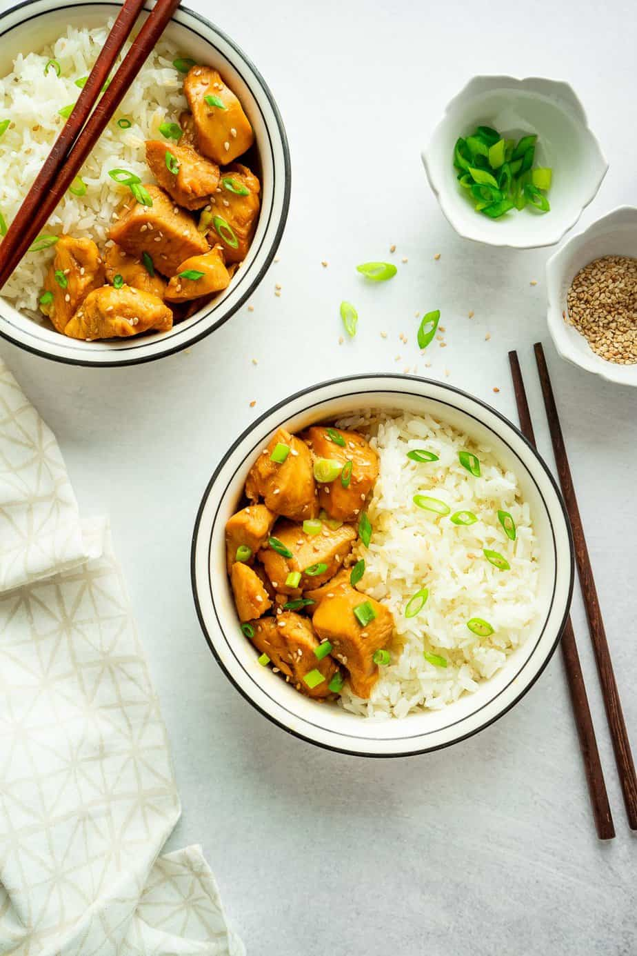 chopstick, chopped green onion in a small bowl, two serving of asian flavor chicken with white rice.