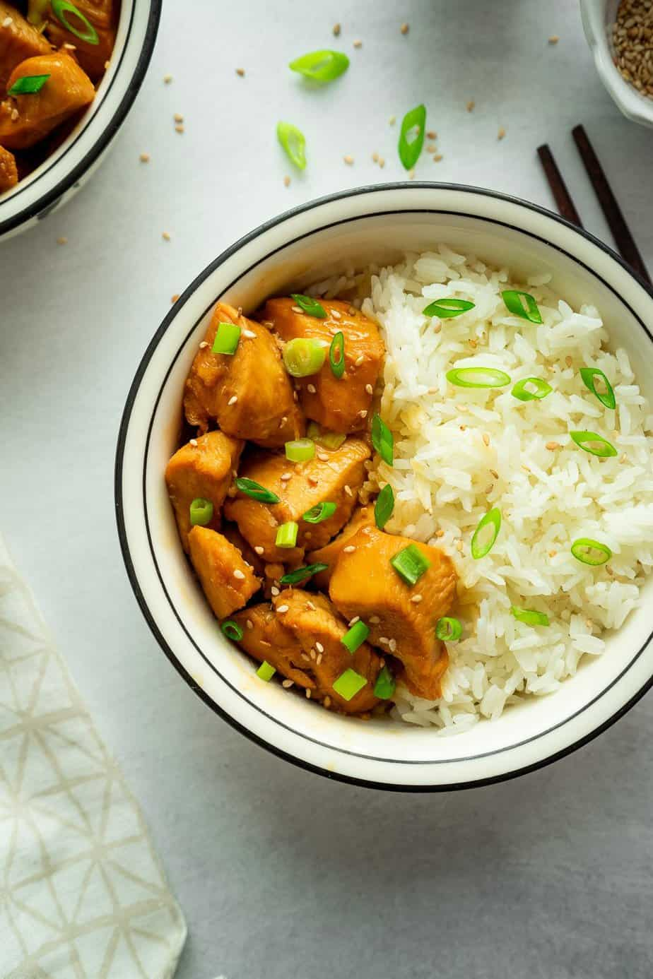 two bowls with white rice, pressure cooker chicken teriyaki with sesame seeds and green onion sprinkle over the rice and chicken pieces.