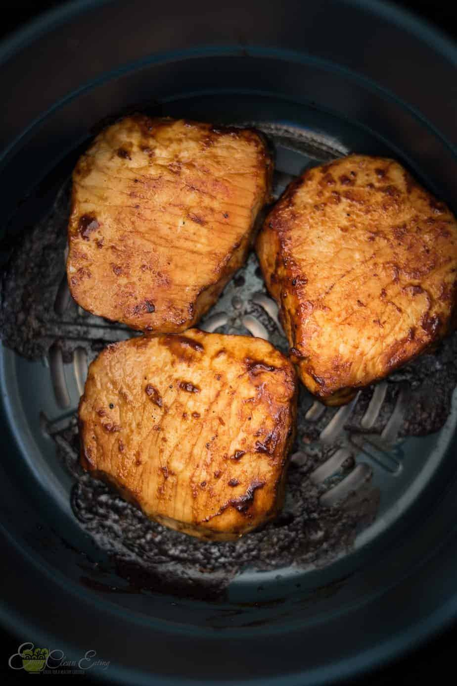 perfectly cooked air fryer pork chops inside the basket.