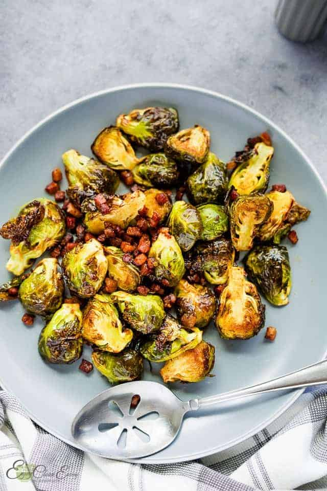 perfectly roasted Brussels sprouts serve on a plate with pancetta and balsamic vinegar