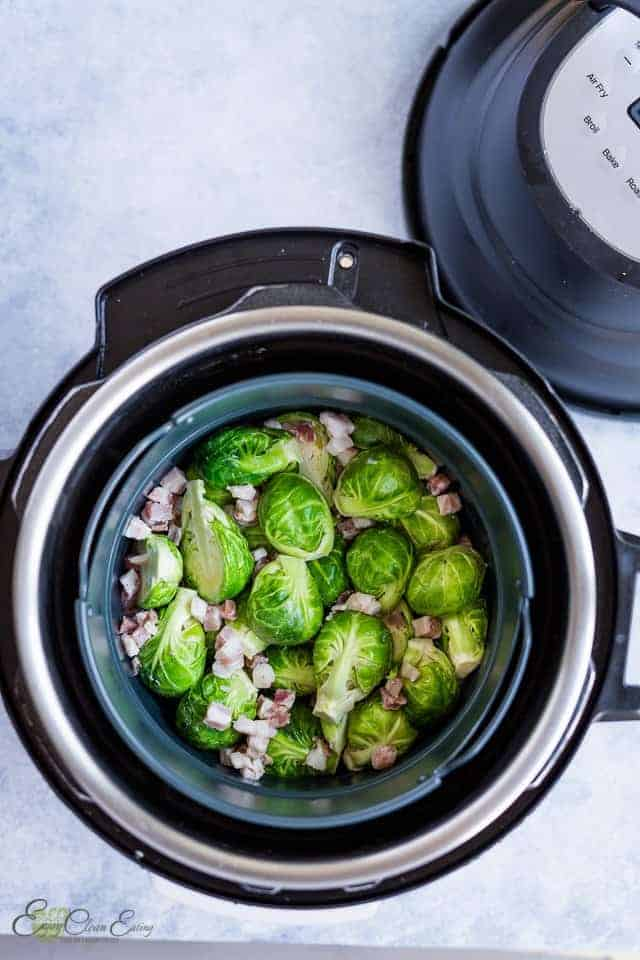 Brussels sprouts with pancetta ready in the air fryer basket before cooking and the instant pot air fryer lid on the side.