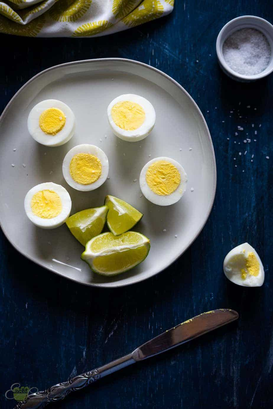 perfectly cooked hard boiled eggs in the air fryer sprinkle with salt and some wedges of lime, a bowl with salt and a bite egg.