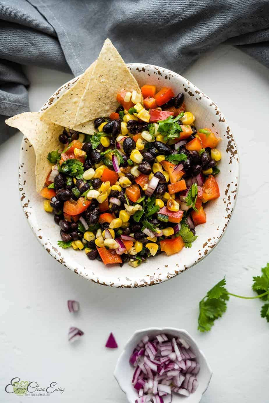 The salsa was serve with tortilla chips on the side there is chopped red onion in a white small bowl, cilantro and some chips on the side.