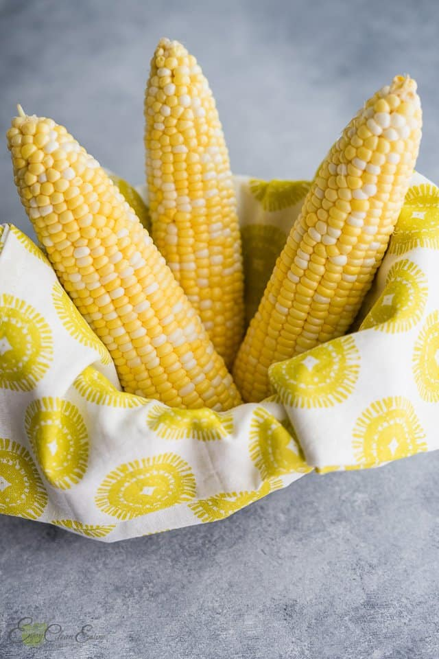 fresh corn on the cob with husks and silks removed in a small basket and kitchen towel.