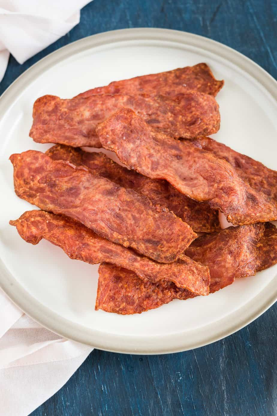 air fryer turkey bacon on a plate and a napkin on the side
