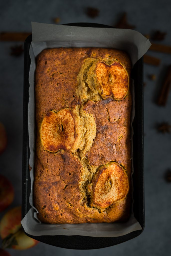 Freshly bake apple bread with slices of apple on top and some fall spices on the background