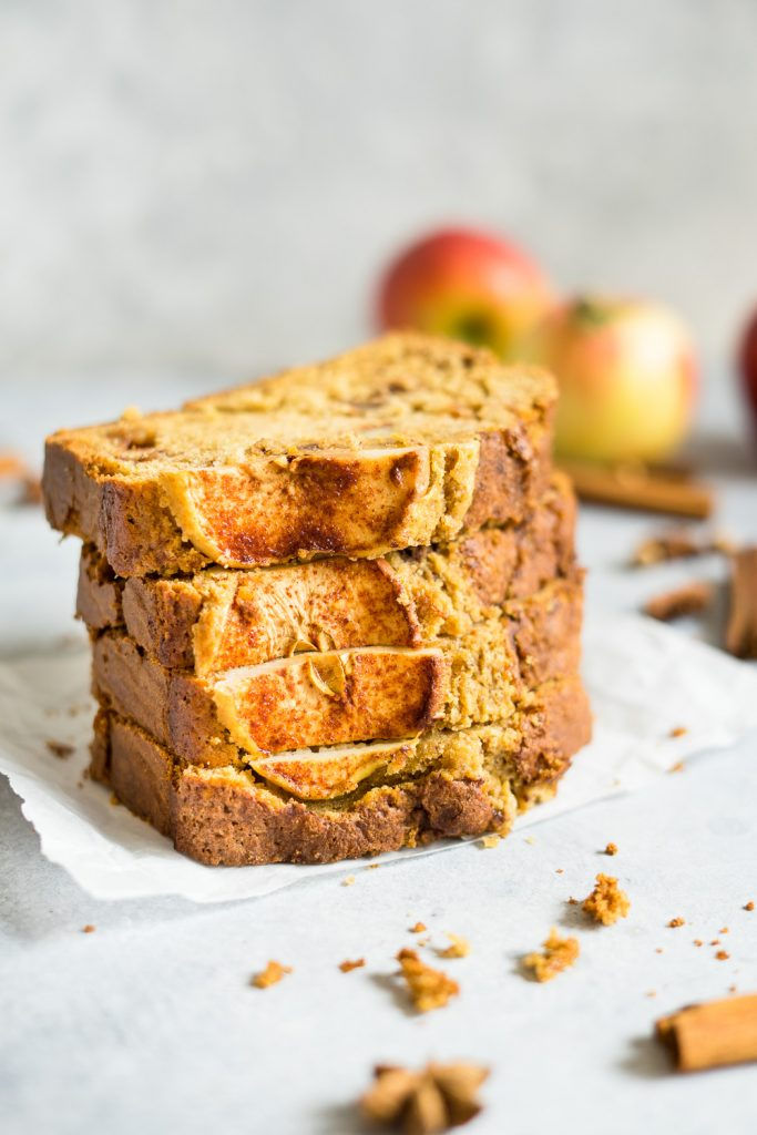 Slices of cinnamon apple bread recipe, some scrambled around and some apples and fall spices on the background.