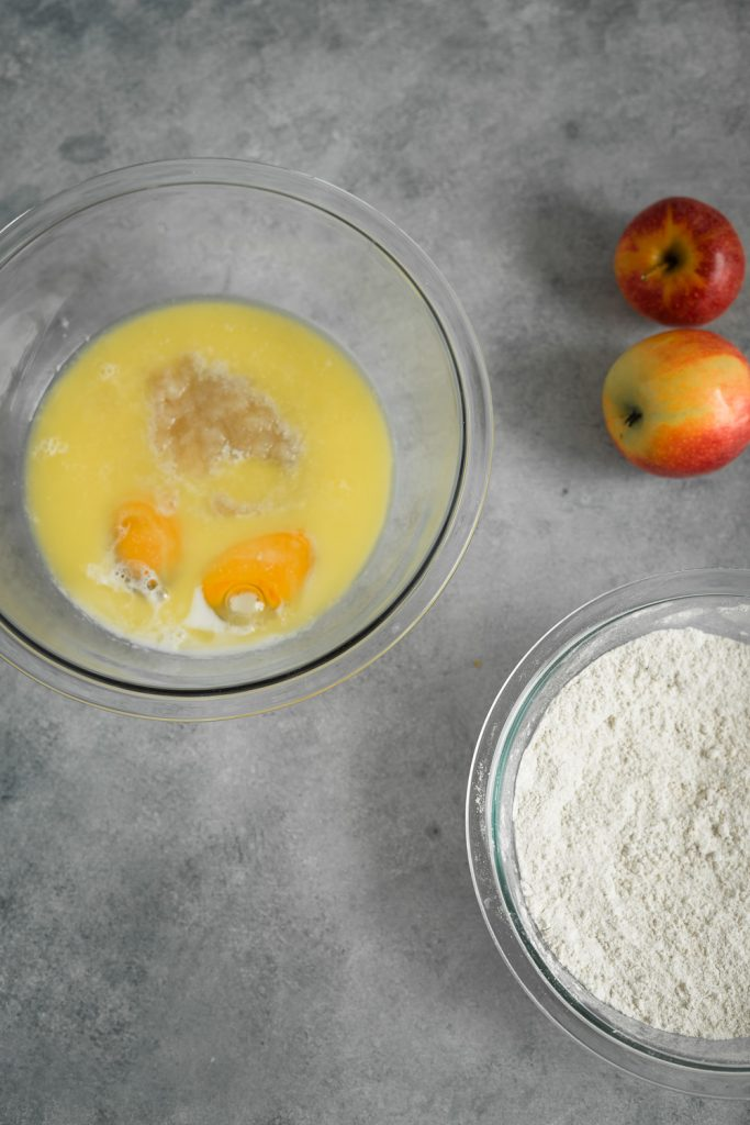 The ingredients to make apple cinnamon bread in bowls, the wet mixture ingredients in one bowl and the dried ingredients in another bowl and couple apples in the back ground