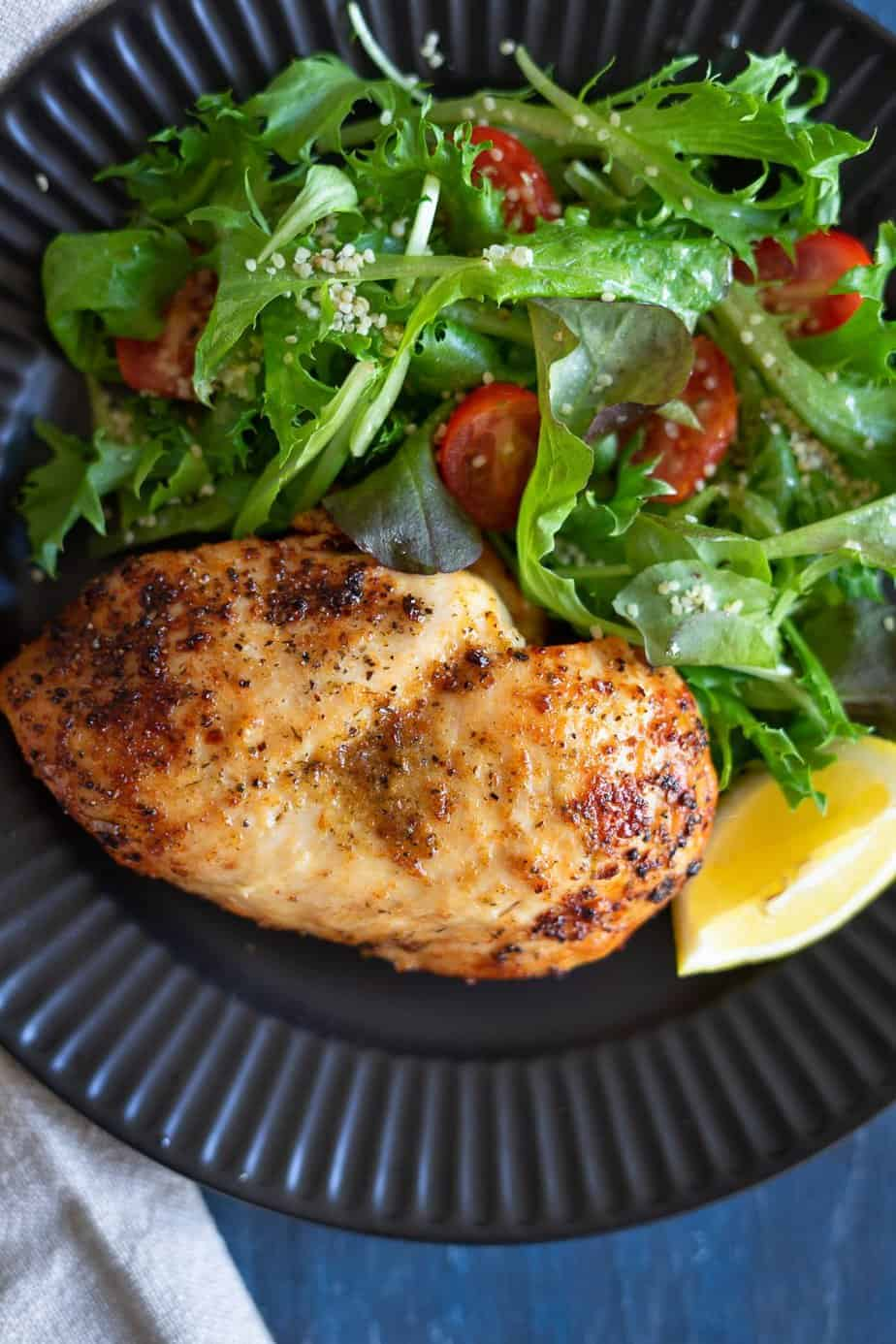 perfectly cooked frozen chicken breast served with a salad of baby lettuces mix and cherry tomatoes.