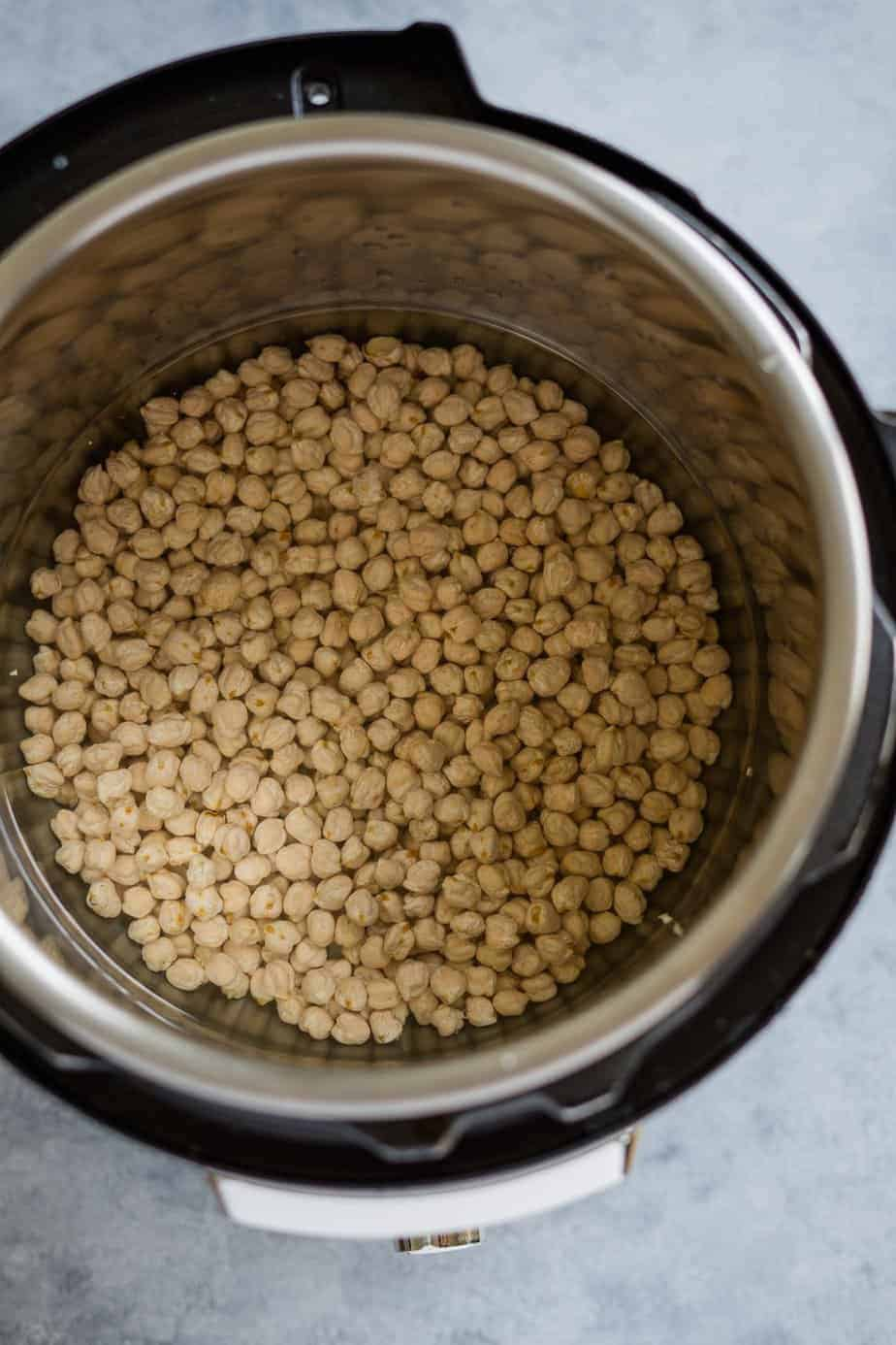 dried chickpeas with water inside the instant pot to pressure cook and make homemade hummus.