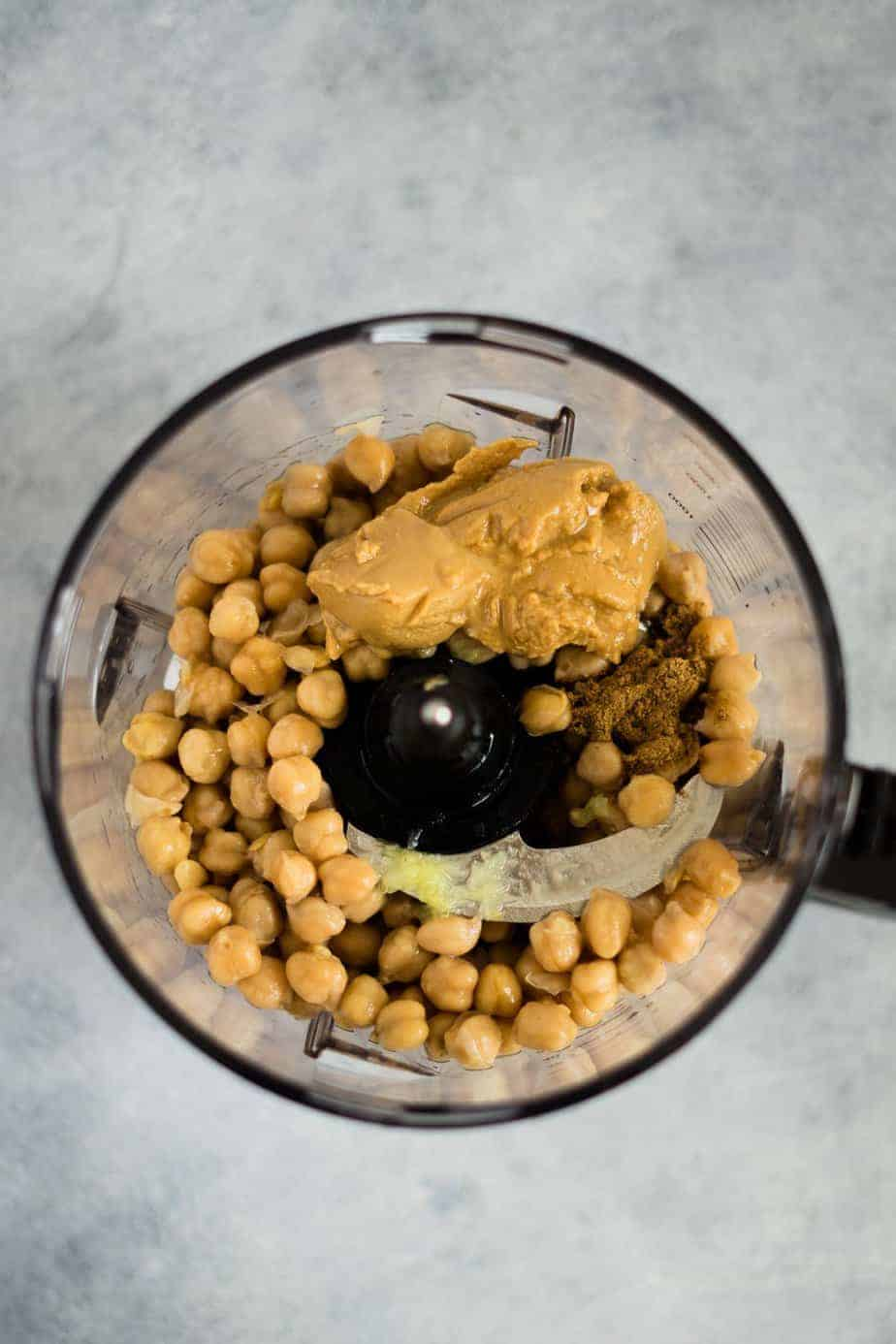 garbanzo beans inside the ninja food processor with the ingredients to make instant pot hummus