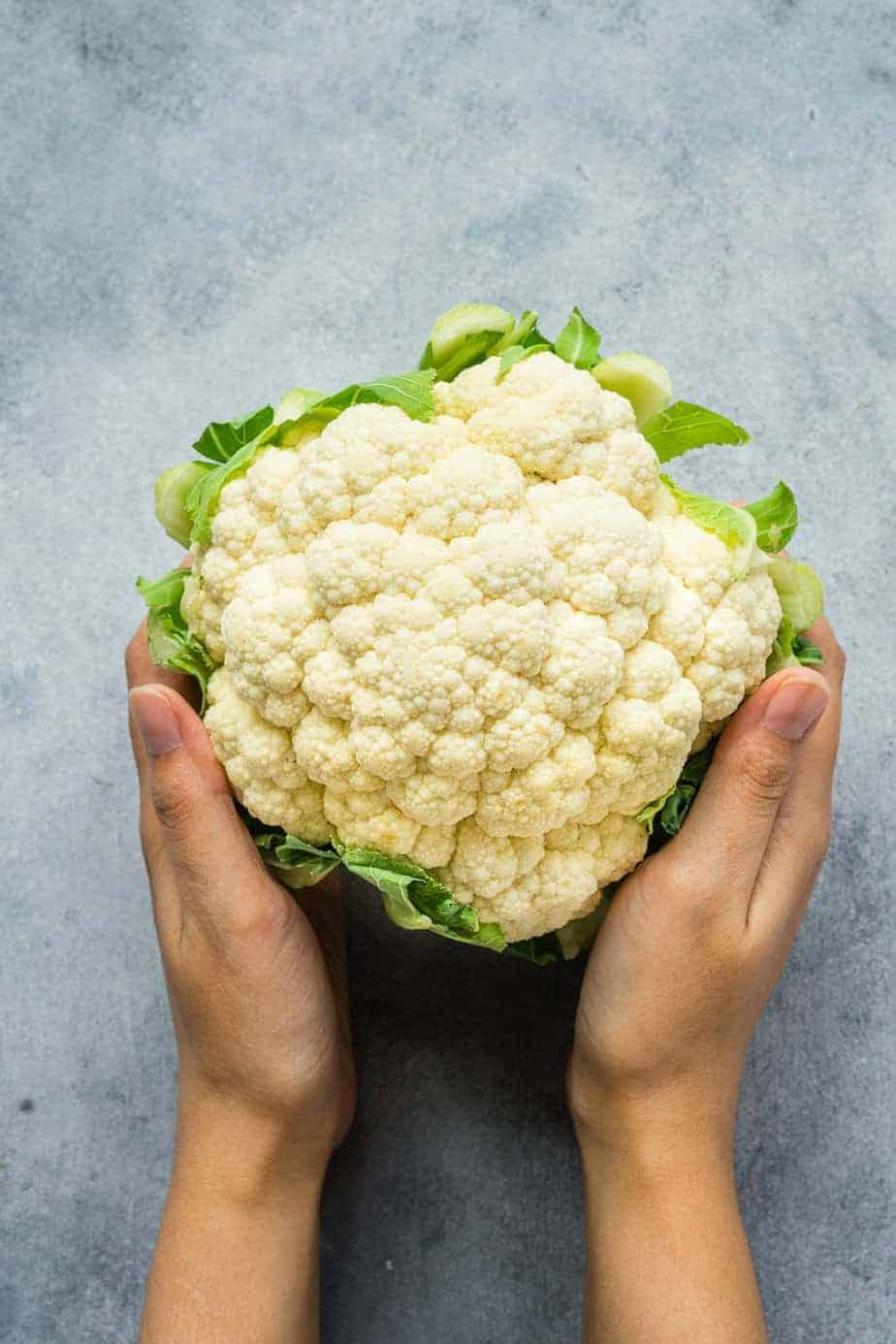 holding a head of cauliflower with both hands.