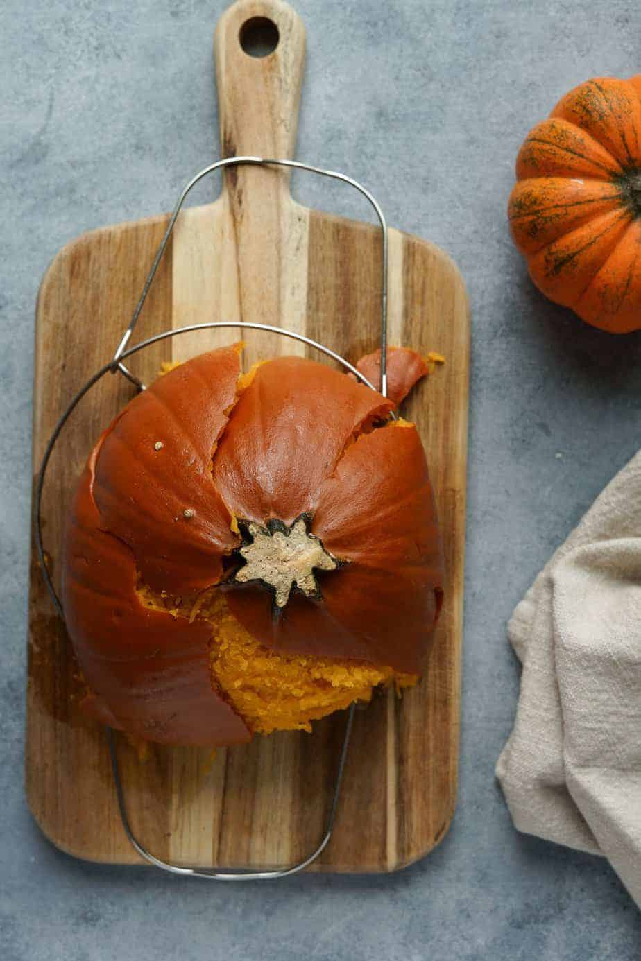Move the cooked pumpkin to a cutting board with the help of the trivet.