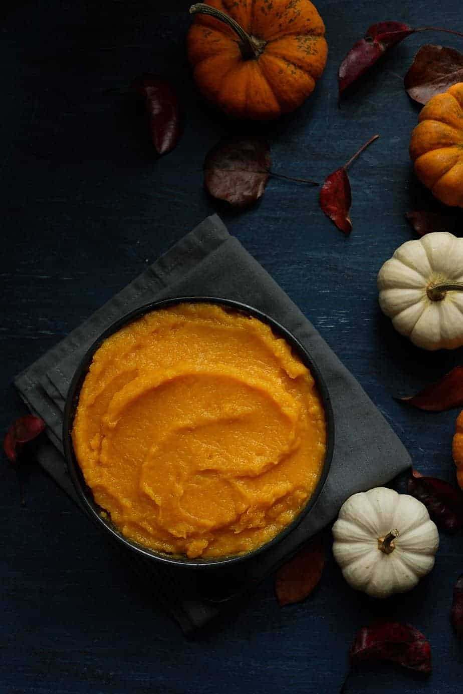 Fresh homemade pumpkin puree made using the instant pot pressure cooker. serve in a bowl to be store in the refrigerator around the bowl, there are pumpkins and leaves