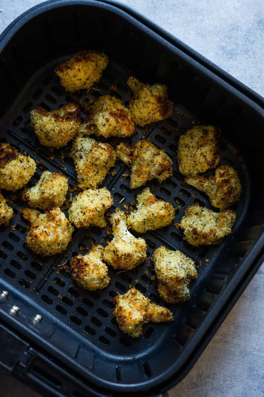 perfectly crispy cauliflower bites inside the air fryer basket after cooking.