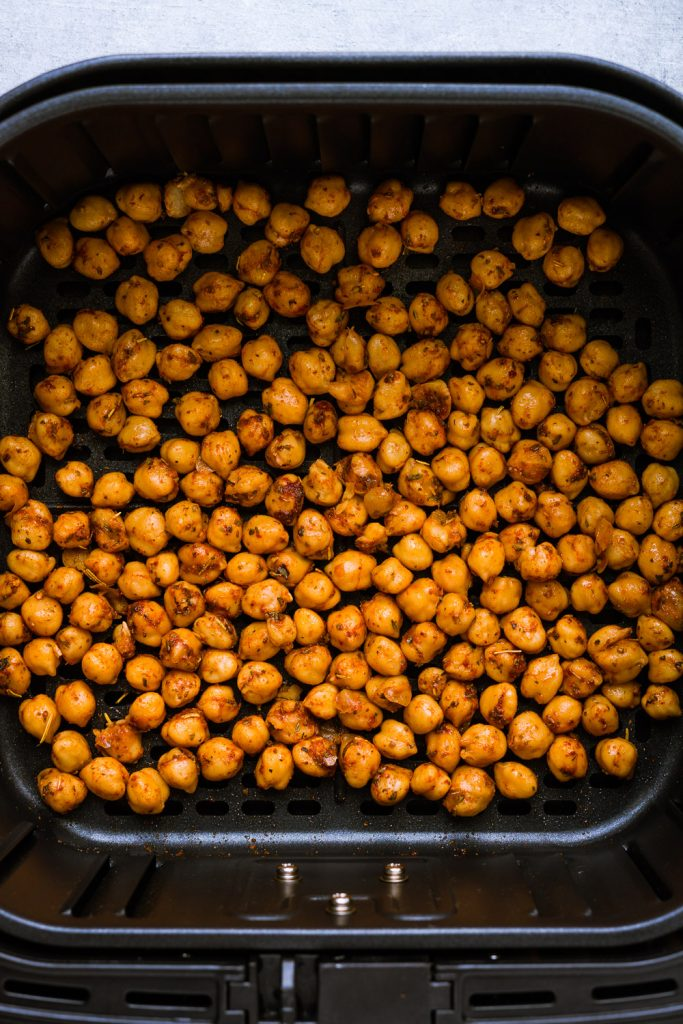 seasoned chickpeas in the air fryer basket before cooking.