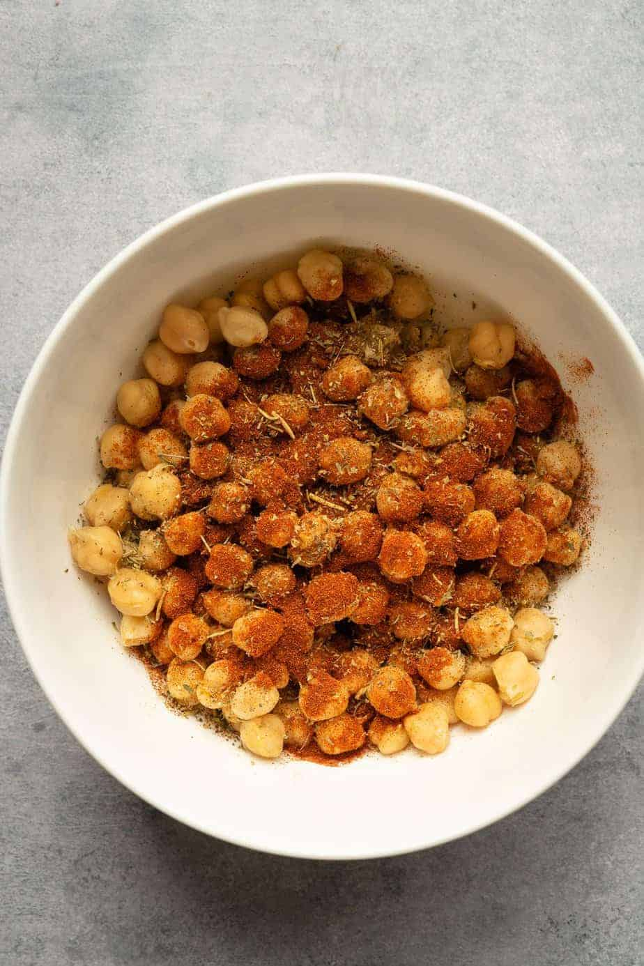 ingredients to make crispy chickpeas in the air fryer in a bowl before tossing.