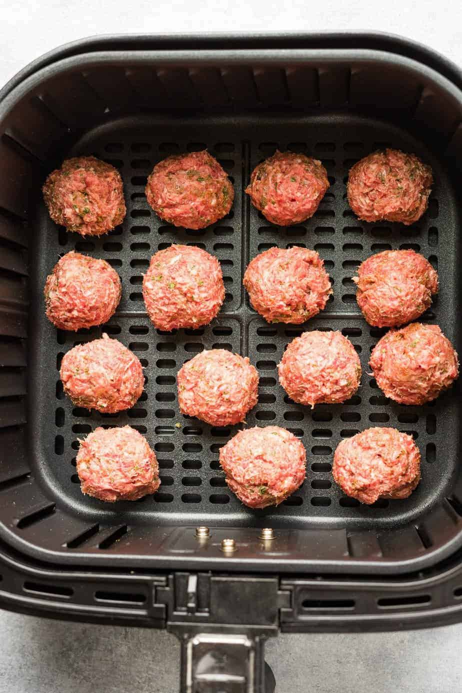 the lamb meatballs inside the air fryer basket before cooking