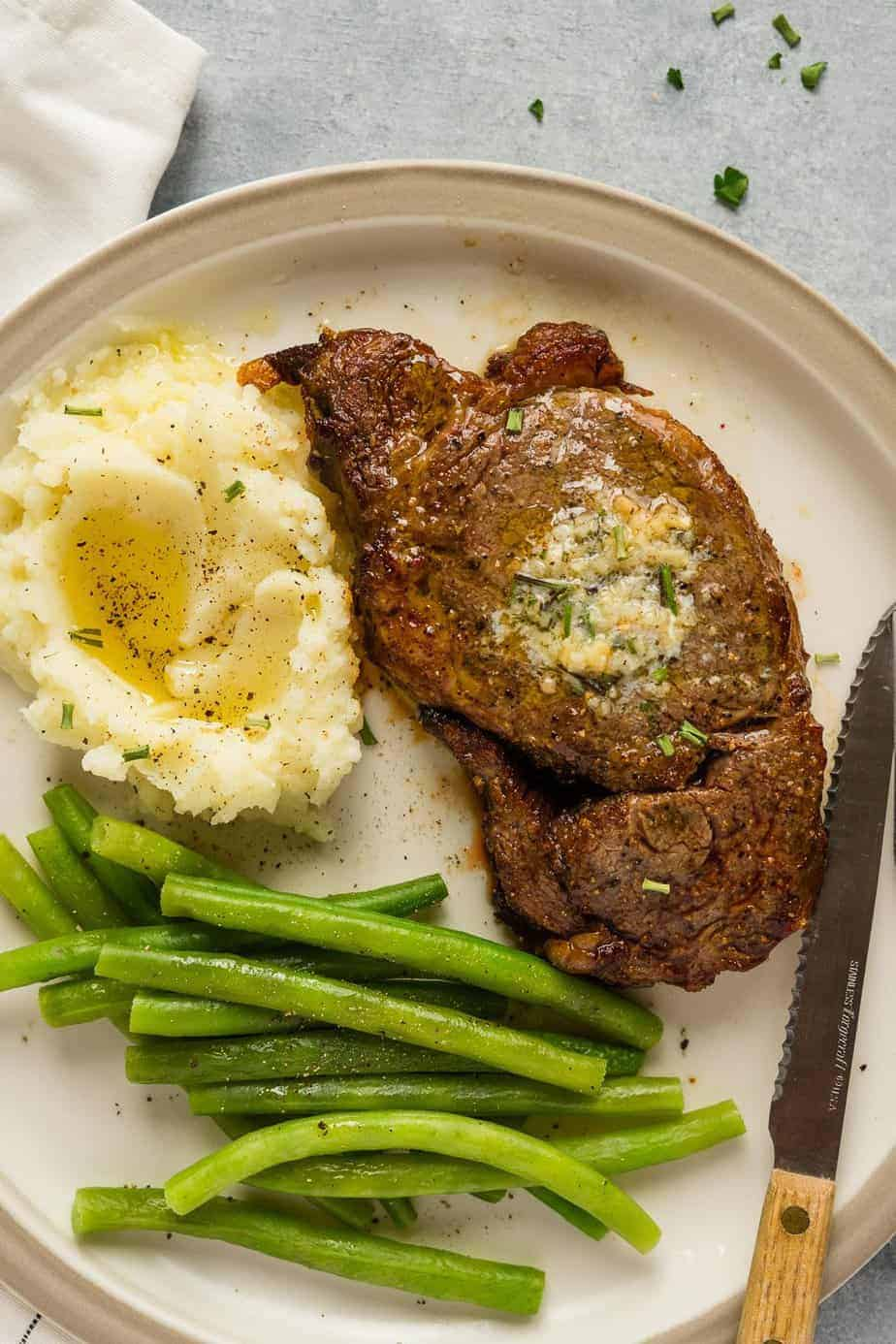 ribeye steak in the air fryer served with mashed cauliflower and steamed green beans