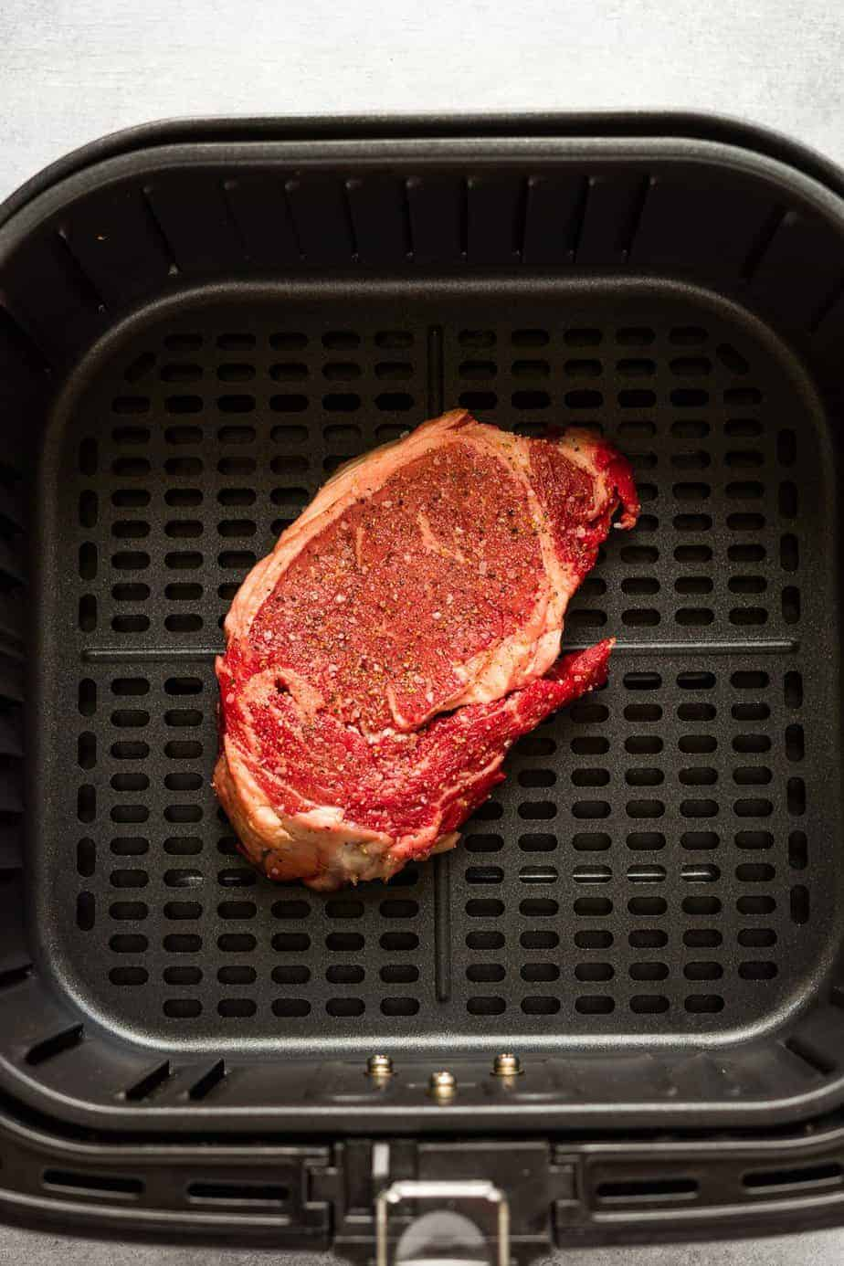 seasoned ribeye steak inside the air fryer basket