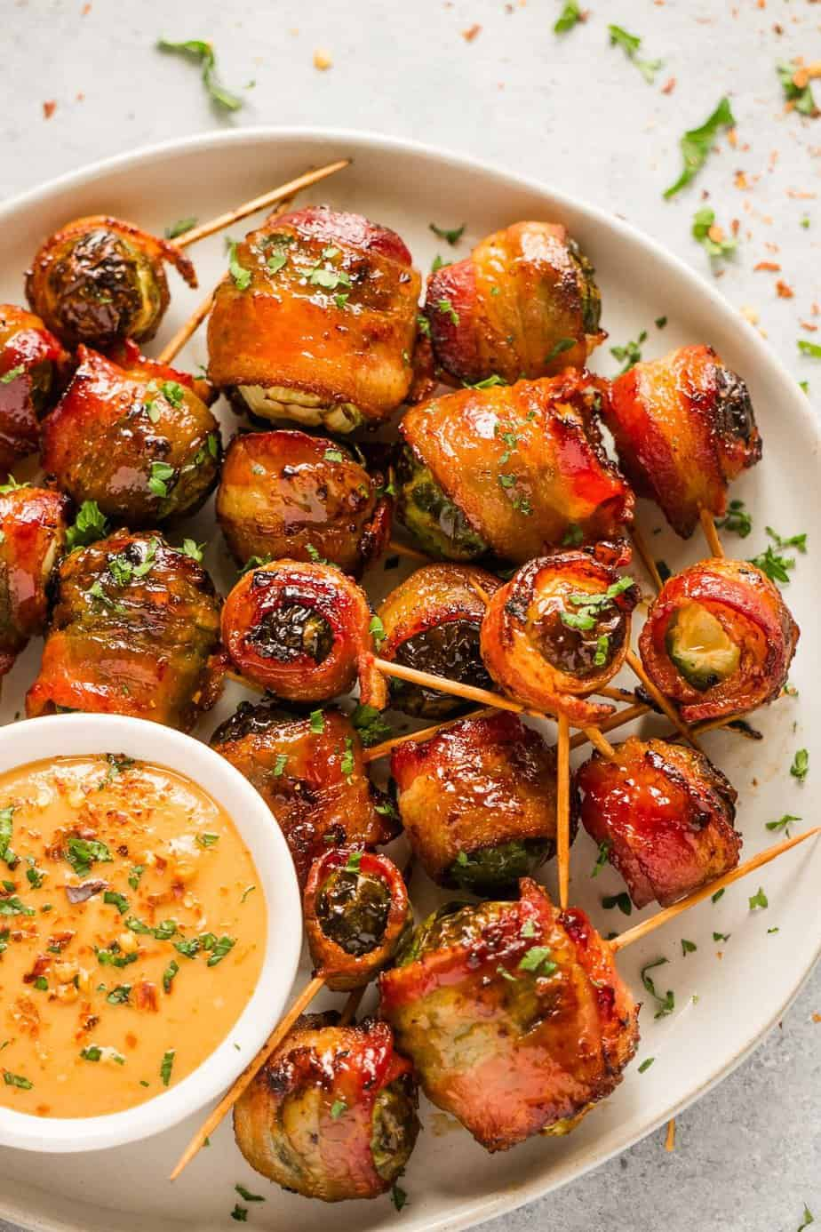 Air fryer bacon wrapped Brussels sprouts serve with tahini sauce.