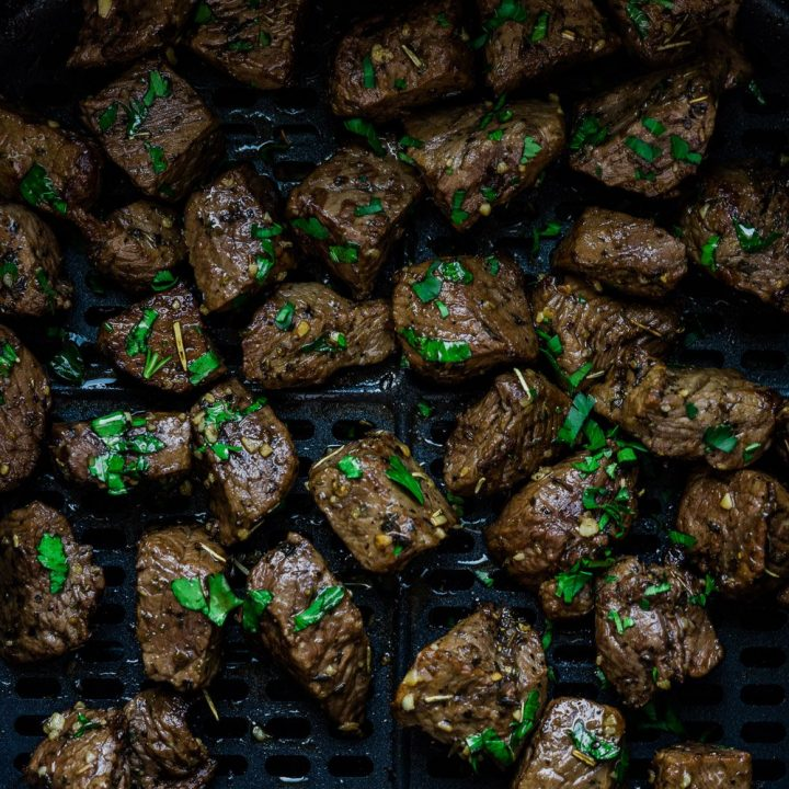 Air fryer steak bites inside the basket and garnish with parsley.