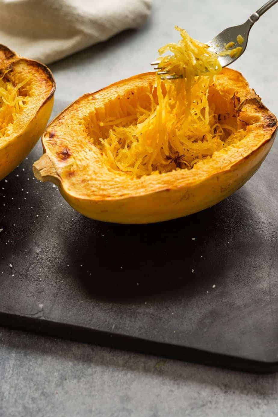 Air fryer Spaghetti squash holding the noodles with a fork.