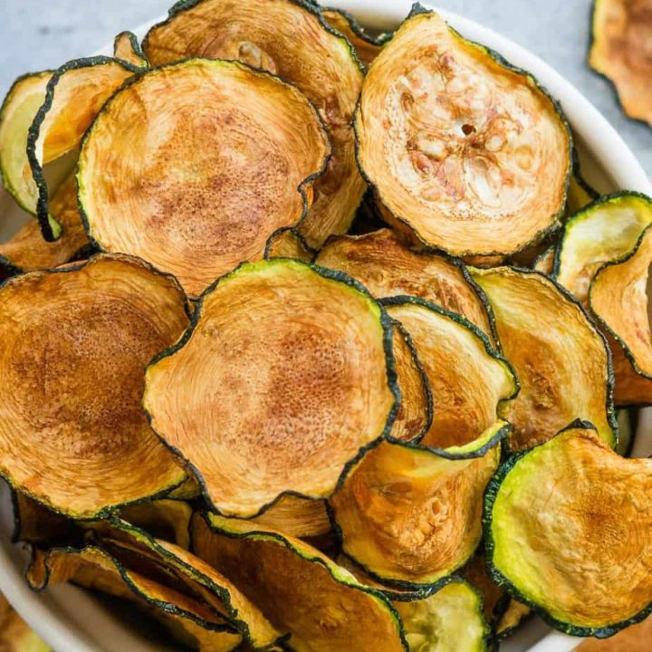 Crispy air fryer zucchini chips in a bowl.