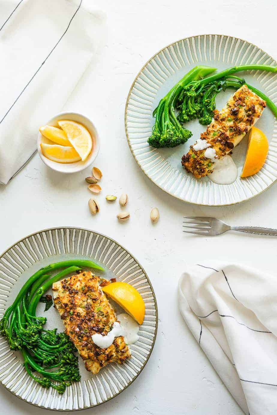 Air fryer halibut with pistachios crust serve with broccolini and lemon wedges.