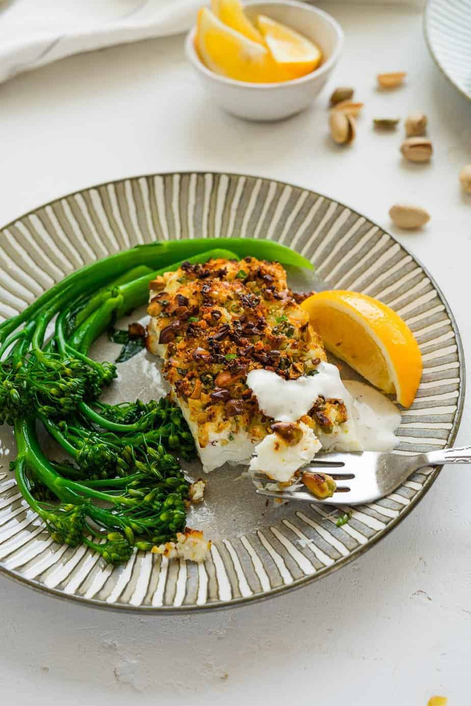 Perfectly cooked fish serve with a side of broccolini and lemon wedges.