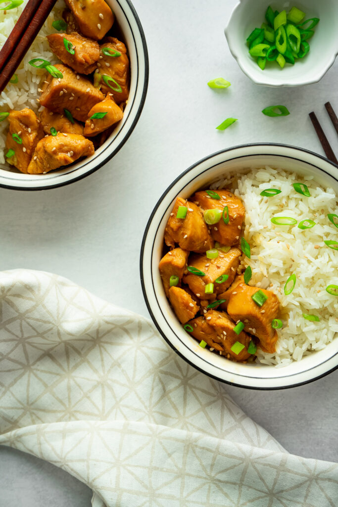 instant pot chicken teriyaki serve with white jasmine rice, sprinkle with green onion and sesame seeds. serve in two bowls and couple chopsticks.