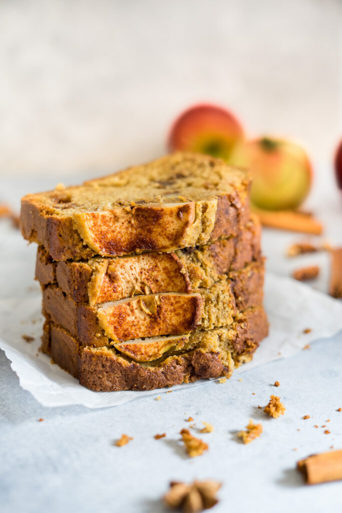 Slices of apple bread holding one with the fingers and some scrambled around and some apples in the background.
