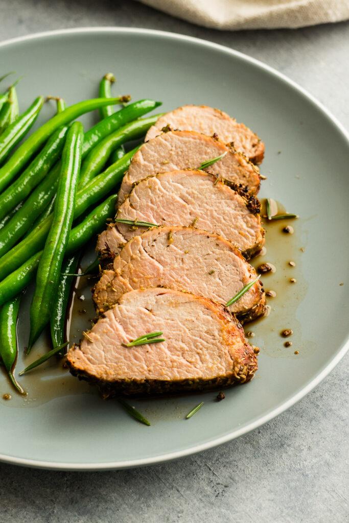 Pork tenderloin in air fryer serve with sautéed green beans.