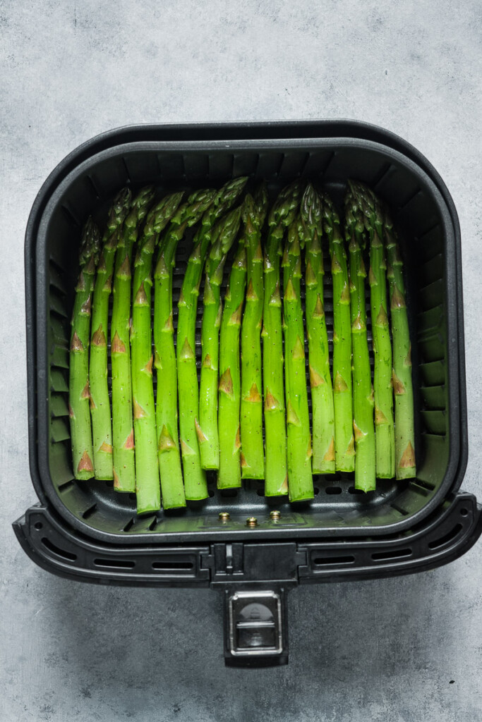 Before cooking the seasoned asparagus in the air fryer basket.