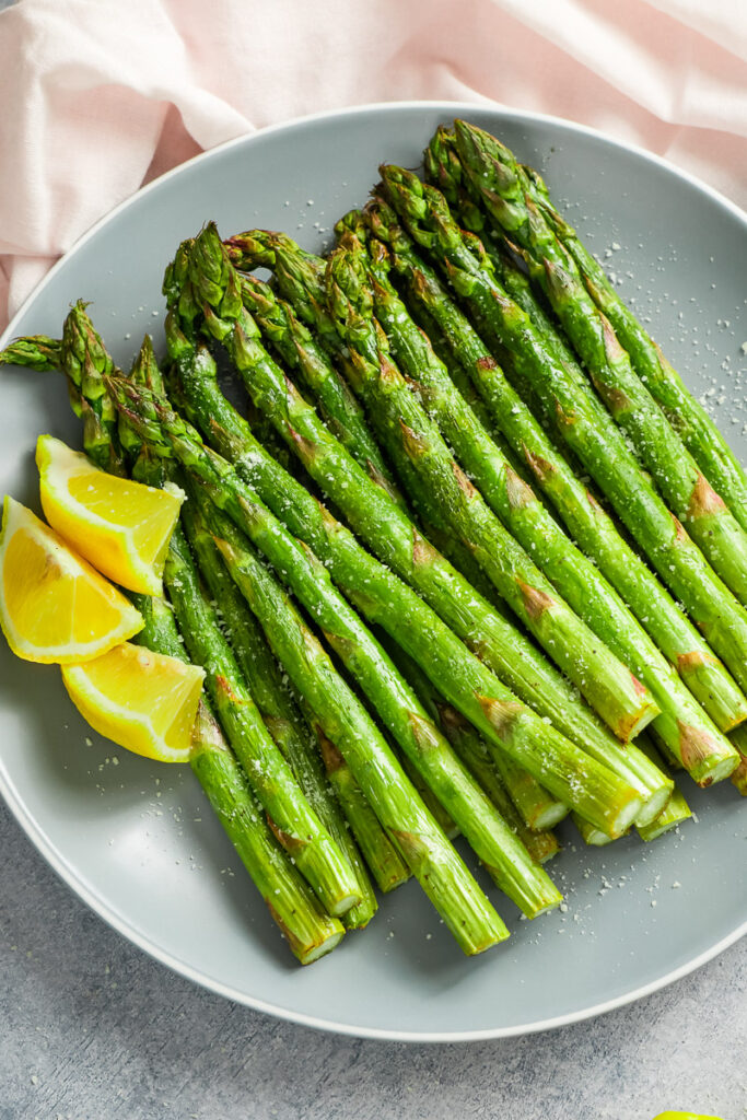 Perfectly cooked air fryer asparagus. served with lemon and sprinkle with grated parmesan cheese.