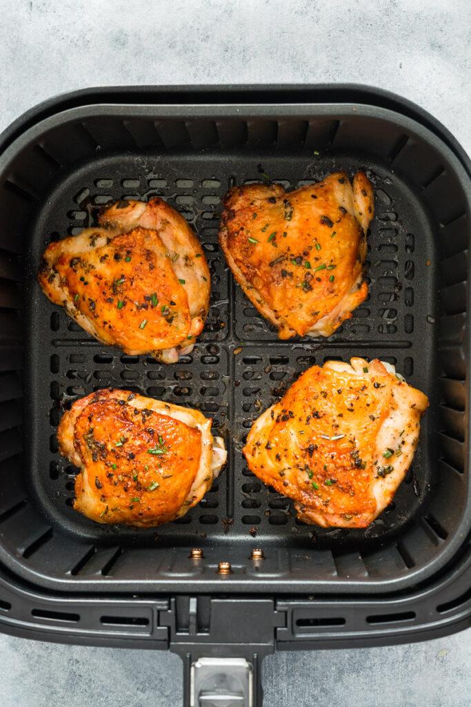 Air fryer Chicken Thighs bone in skin on inside the basket.