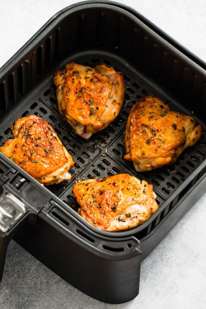 Crispy skin chicken thighs inside the air fryer basket.