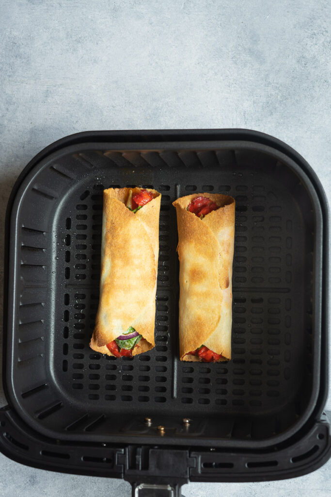 taquitos in the air fryer basket after cooking.