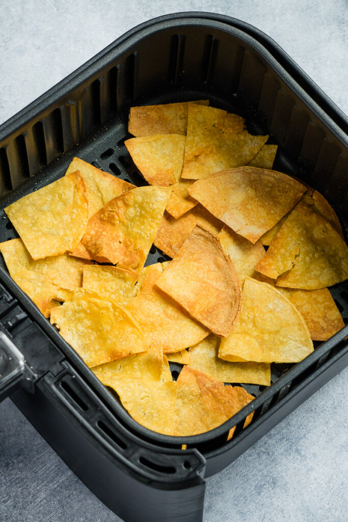 tortillas chips in the air fryer basket after cooking.