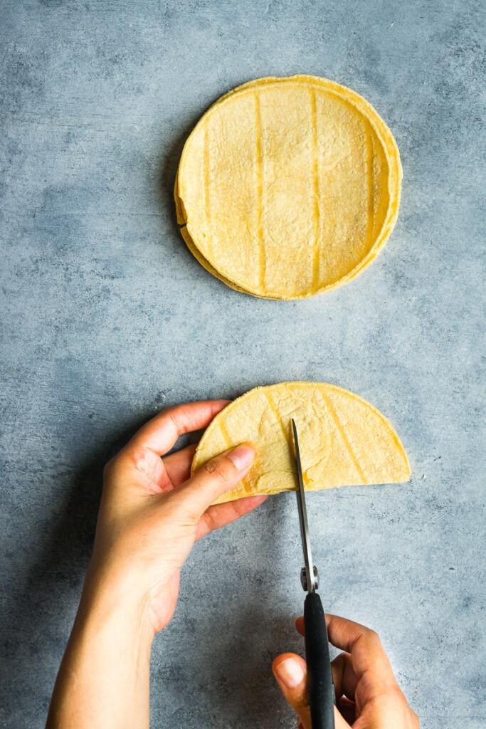 Cutting corn tortilla in triangles.