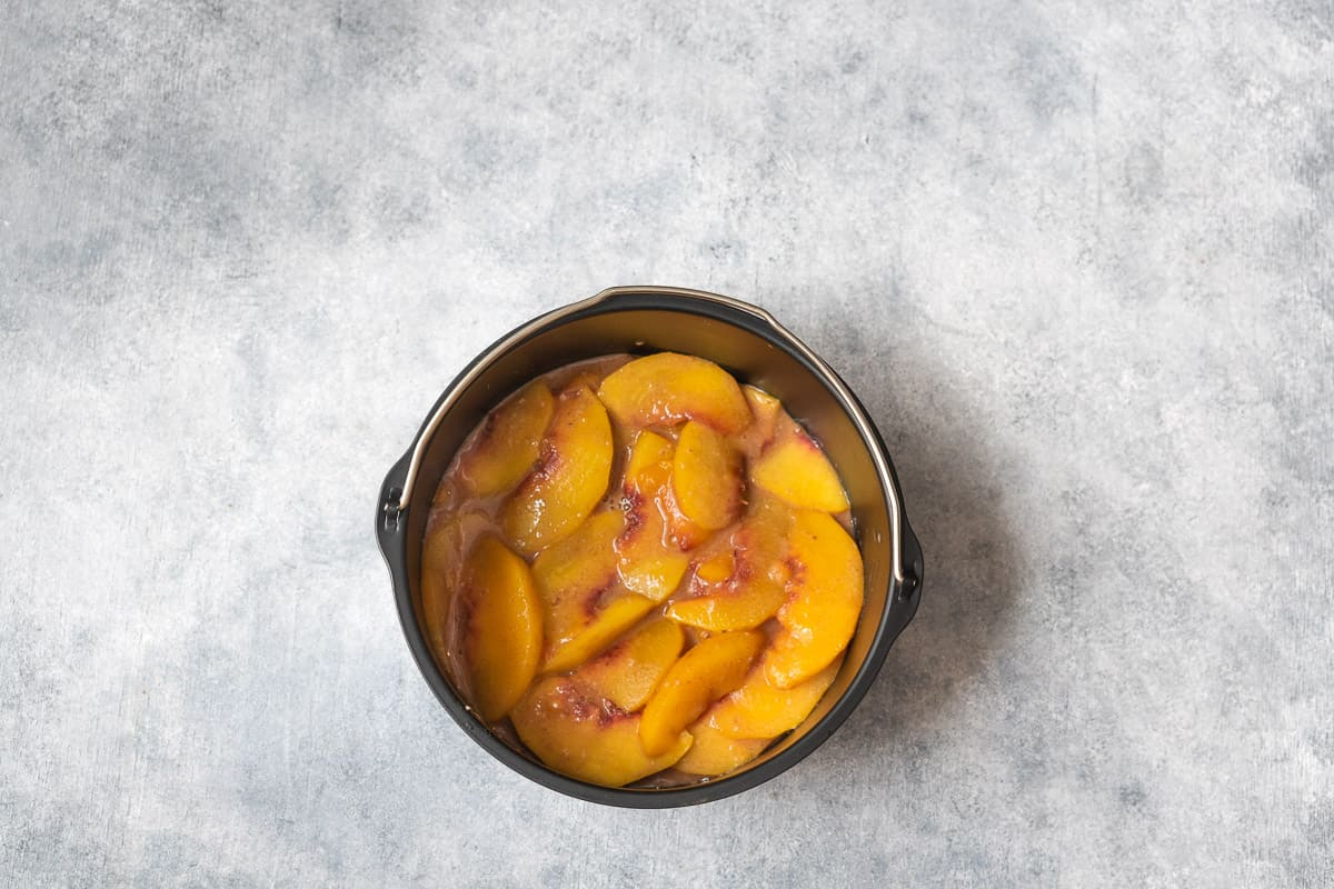 mixing the peach slices in a 7 inches baking dish.