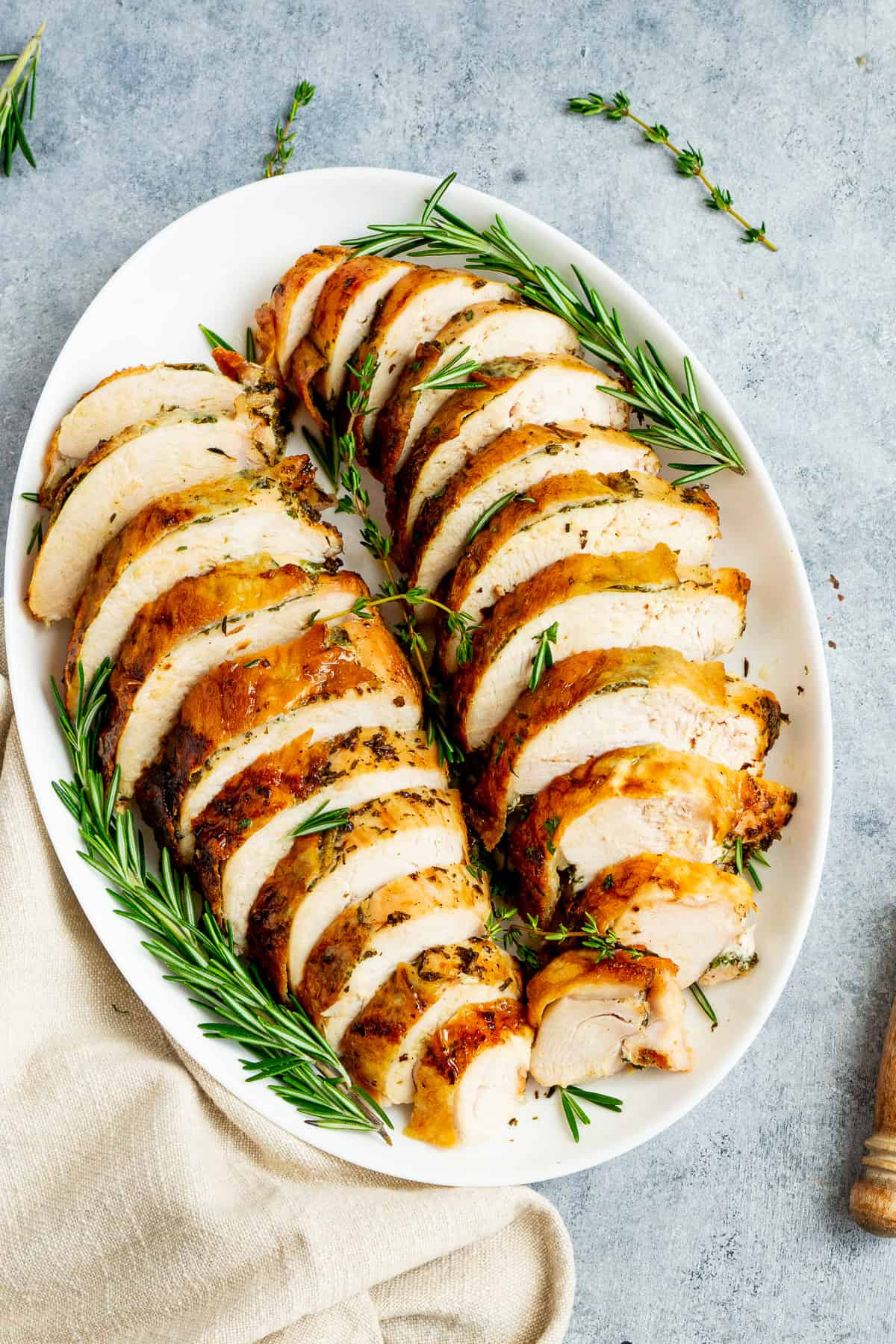 Air fryer roasted turkey breast sliced on a plater with fresh thyme and rosemary.
